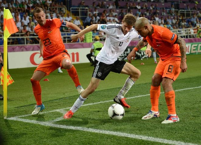 German forward Thomas Mueller (C) vies with Dutch midfielder Rafael van der Vaart (L) and midfielder Nigel de Jong during the Euro 2012 championships football match the Netherlands vs Germany on June 13, 2012 at the Metalist Stadium in Kharkiv. Germany won 2-1.     AFP PHOTO/ PATRIK STOLLARZPATRIK STOLLARZ/AFP/GettyImages