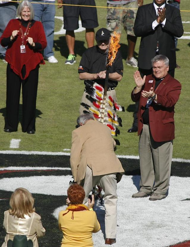 As Florida State president Eric Barron, right, and his wife Molly, top left, applaud, former Florida State head coach Bobby Bowden, center, plants the spear on the 50-yard line before an NCAA college football game against North Carolina State, Saturday, Oct. 26, 2013, in Tallahassee, Fla. (AP Photo/Phil Sears)