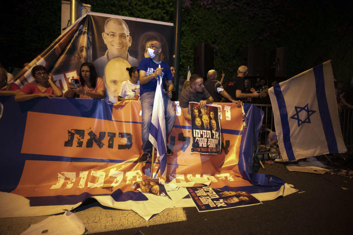 Israeli right-wing protesters chant slogans and hold flags during a demonstration against the forming of a new government in the central Israeli city of Ramat Gan, Wednesday, June 2, 2021. (AP Photo/Sebastian Scheiner)