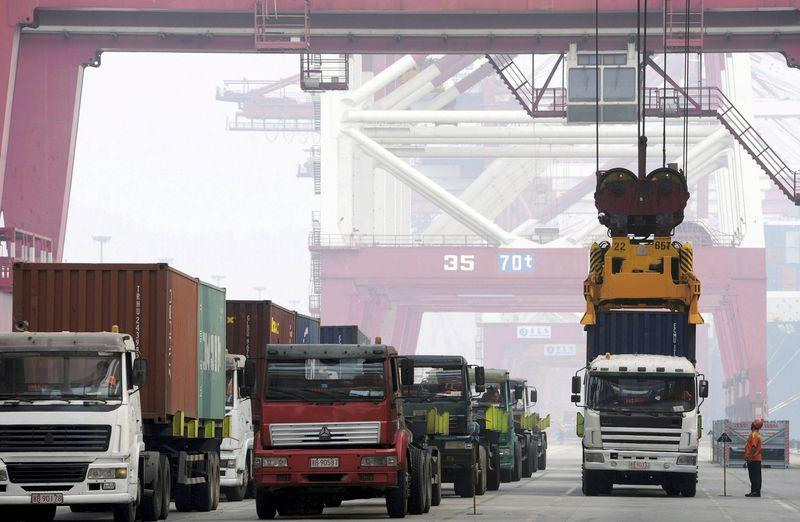 Crane lifts a shipping container from a truck to load it onto a ship at a port in Qingdao, Shandong province, China