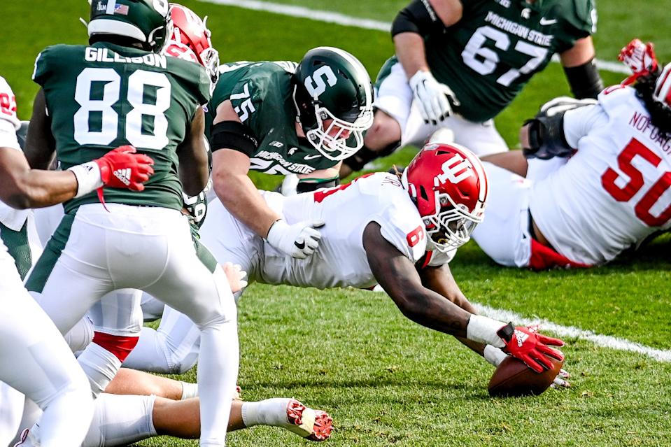 Indiana's James Head Jr., right, recovers a MSU fumble during the first quarter on Saturday, Nov. 14, 2020, at Spartan Stadium in East Lansing. Michigan State's Kevin Jarvis, left, was unable to get to the ball first.