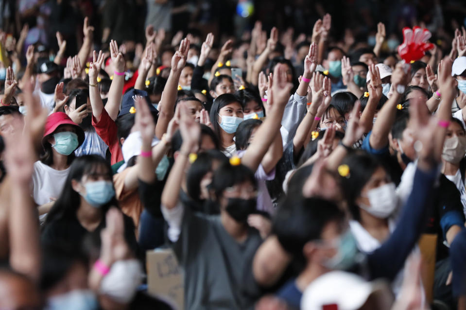 "A crowd flashes the three-finger protest gesture during a student rally in Bangkok Saturday, Nov. 21, 2020. Organized by a group that mockingly calls themselves ""Bad Students,"" the rally calls for educational reforms and also supports the broader pro-democracy movement's demands for constitutional change. (AP Photo/Sakchai Lalit)"
