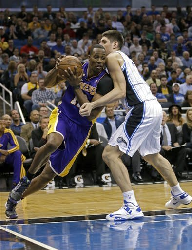 Los Angeles Lakers' Dwight Howard, left, makes a move to the basket around Orlando Magic's Nikola Vucevic, of Montenegro, during the first half of an NBA basketball game, Tuesday, March 12, 2013, in Orlando, Fla. (AP Photo/John Raoux)