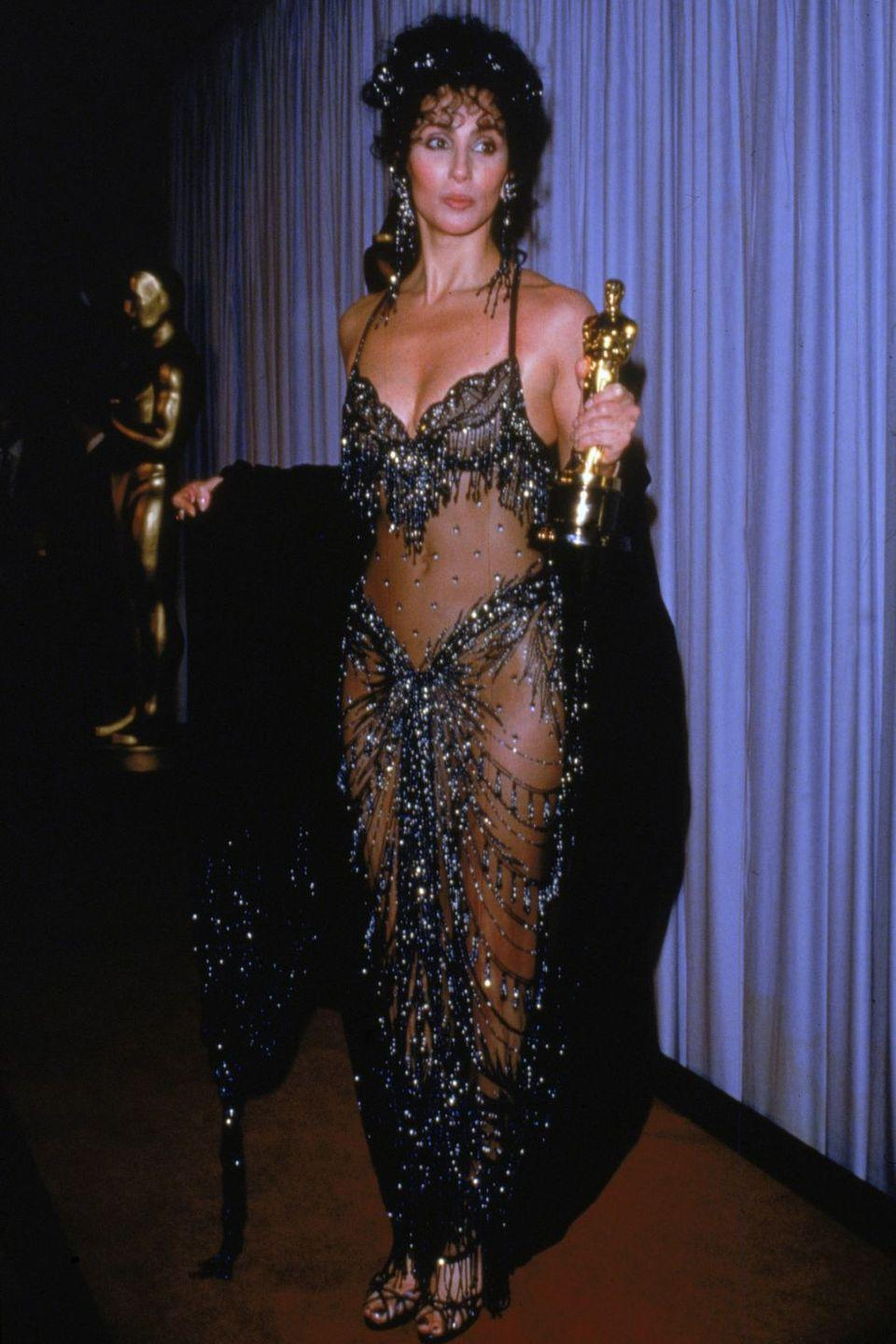 """<p>When Cher arrived at the 1988 Oscars in a tizzy of fringe, beads, and rhinestone-encrusted sheer panels, '80s fashion had just about peaked. Although women weren't stepping out in exact replicas of """"the naked dress,"""" as it's come to be known, it remains an iconic fashion symbol of the era. </p>"""