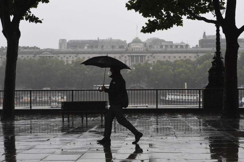 A man walks in the rain along the River Thames Embankment footpath in central London, Friday July 19, 2019. After a period of hot sunny weather, much of Britain is suffering under rain clouds and a cold front.(Stefan Rousseau/PA via AP)