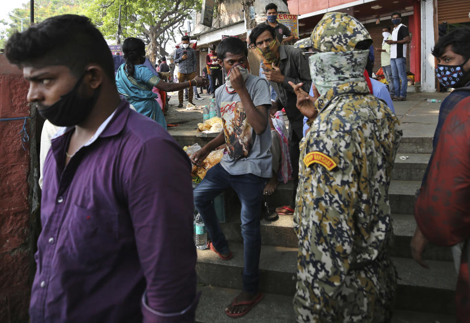 A municipal official, second right, reprimands street vendors for not wearing face masks properly during a lockdown imposed due to rising number of COVID-19 cases in Bengaluru, India, Wednesday, April 28, 2021. India, a country of nearly 1.4 billion people, Wednesday became the fourth nation to cross 200,000 deaths. (AP Photo/Aijaz Rahi)