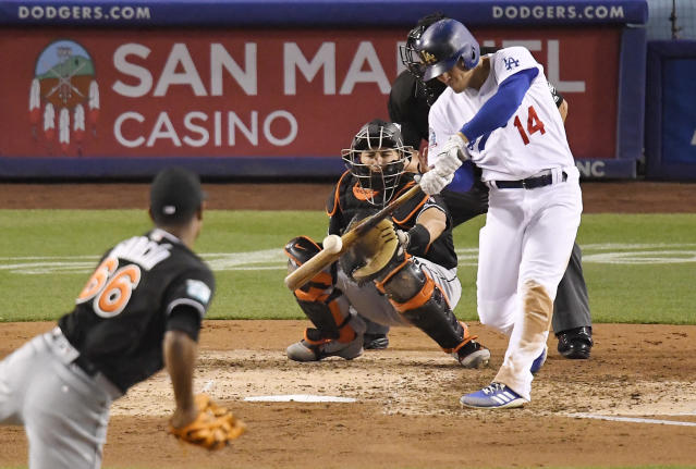 Los Angeles Dodgers' Enrique Hernandez, right, hits a solo home run as Miami Marlins starting pitcher Jarlin Garcia, left, and catcher J.T. Realmuto watch during the fourth inning of a baseball game Monday, April 23, 2018, in Los Angeles. (AP Photo/Mark J. Terrill)