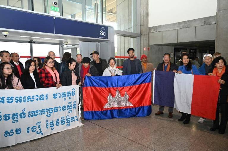 """A few dozen supporters greeted Rainsy in the terminal building, including a handful of Buddhist monks with a banner supporting the return of """"Mr Rainsy to the mother country"""""""