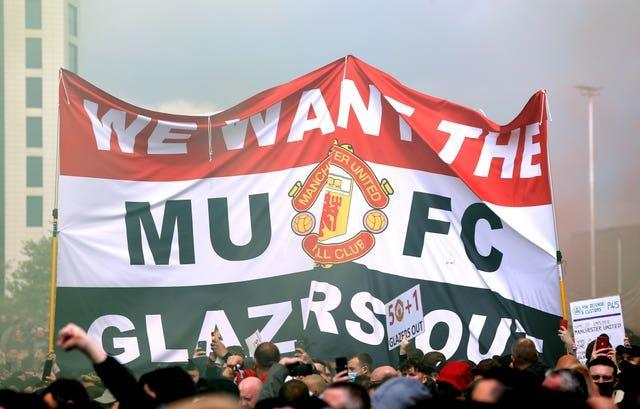 Fans hold up a banner as they protest against the Glazer family