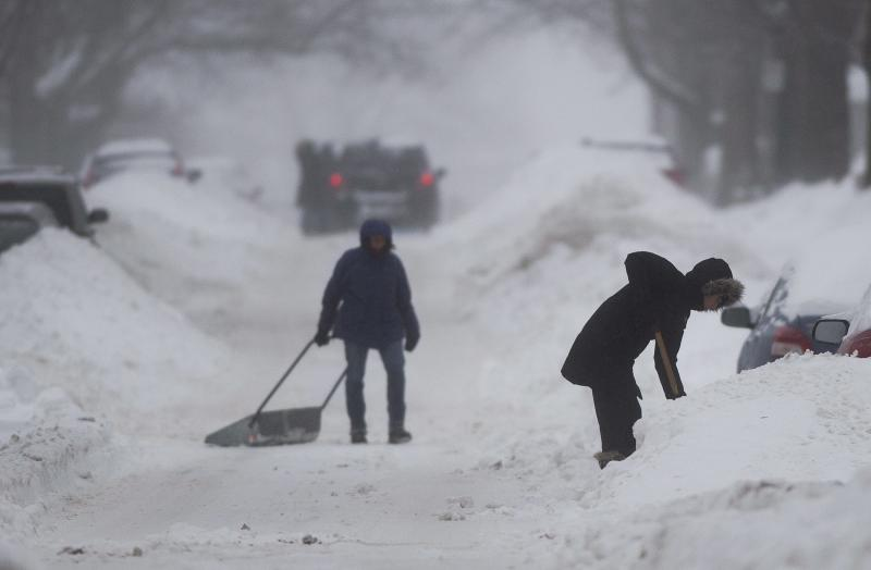 People clear snow from around their cars on a street in Montreal Sunday, Dec. 22, 2013 as a winter storm warning has been issued for the region. (AP Photo/The Canadian Press, Graham Hughes)