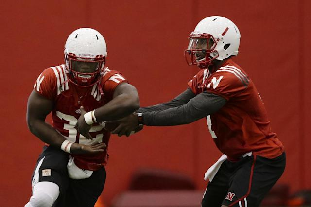 Nebraska quarterback Tommy Armstrong Jr., right, fakes a handoff to running back Imani Cross (32) on the first day of sping NCAA college football practice in Lincoln, Neb., Saturday, March 8, 2014. (AP Photo/Nati Harnik)
