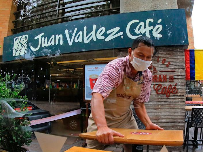 "An employee prepares the terrace of a coffee shop to reopen in Bogota on August 14, 2020. <p class=""copyright"">DANIEL MUNOZ/AFP via Getty Images</p>"