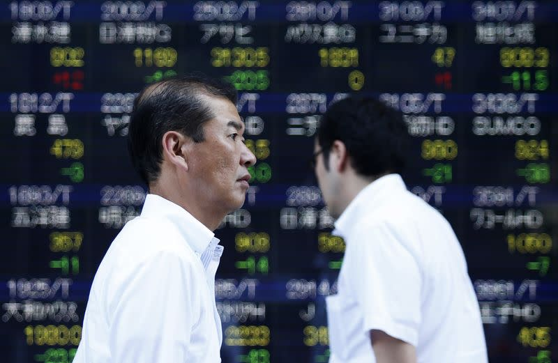 Pedestrians walk past an electronic board showing the various stock prices outside a brokerage in Tokyo