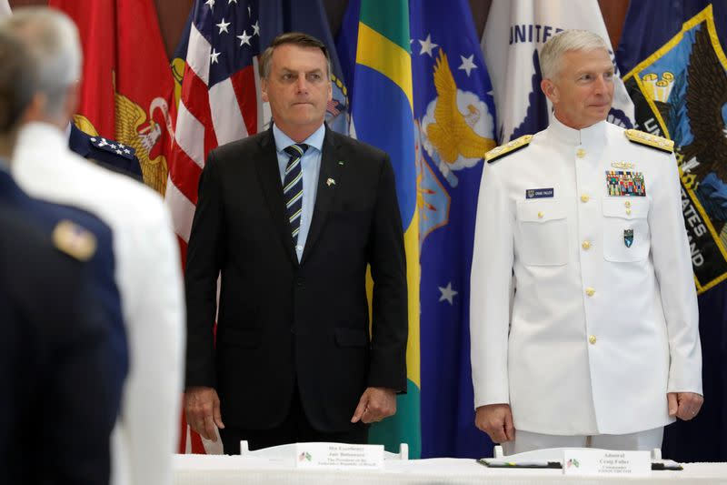 Brazilian President Jair Bolsonaro and Commander of the U.S. Southern Command Admiral Craig S. Faller attend an agreement signing ceremony, in Miami