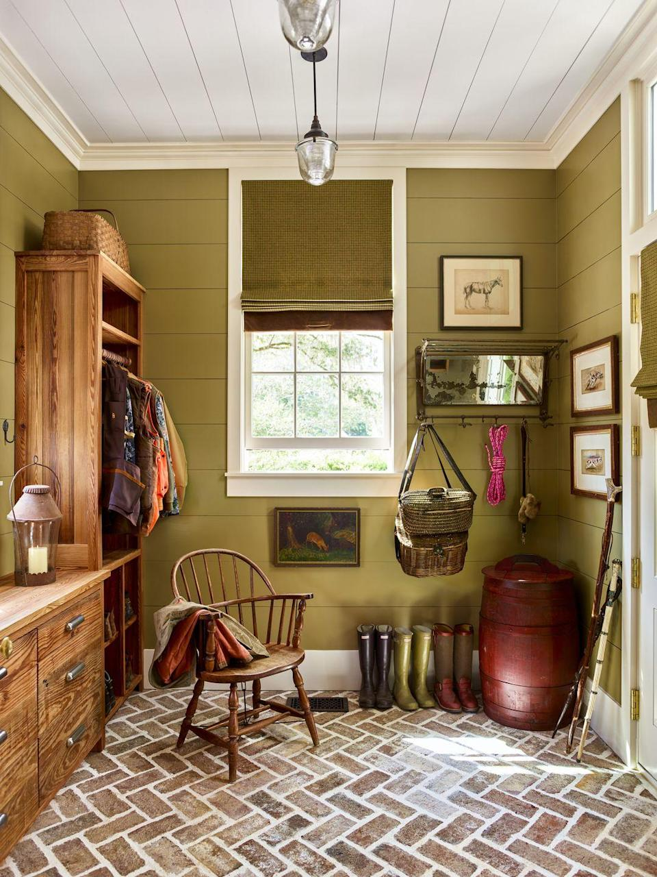 """<p>With floors these gorgeous, the walls in this mini mudroom need to pack just as big of an impact. A soft olive green like <a href=""""https://www.sherwin-williams.com/homeowners/color/find-and-explore-colors/paint-colors-by-family/SW6705-high-strung"""" rel=""""nofollow noopener"""" target=""""_blank"""" data-ylk=""""slk:High Strung by Sherwin-Williams"""" class=""""link rapid-noclick-resp"""">High Strung by Sherwin-Williams</a> sets the scene for a day full of fun outdoor activities.</p>"""