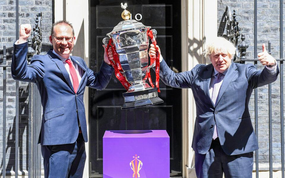 Rugby League World Cup chief executive Jon Dutton with Prime Minister Boris Johnson and the Paul Barriere trophy - Simon Wilkinson/SWpix.com