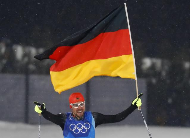 Nordic Combined Events - Pyeongchang 2018 Winter Olympics - Men's Team 4 x 5 km Final - Alpensia Cross-Country Skiing Centre - Pyeongchang, South Korea - February 22, 2018 - Johannes Rydzek of Germany waves the German flag as he crosses the finish line. REUTERS/Kai Pfaffenbach