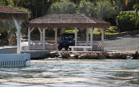 A man in a golf cart is seen at a dock in Little St. James Island, one of the properties of financier Jeffrey Epstein, near Charlotte Amalie - Credit: Reuters