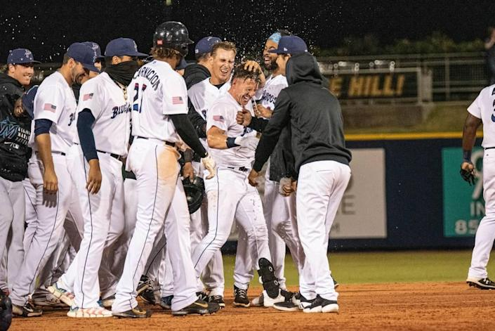The Pensacola Blue Wahoos celebrate after Peyton Burdick hits a walk-off double in the 10th inning against the Rocket City Trash Pandas on Tuesday, May 18, 2021.