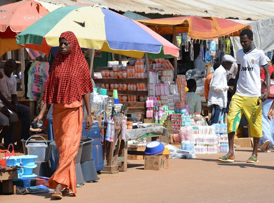 A Muslim woman walks past a stall in a market in Bangui on October 2, 2014, as Muslim traders, who fled at the start of the year to neighbouring Cameroon and Chad, return home (AFP Photo/Pacome Pabamdji)