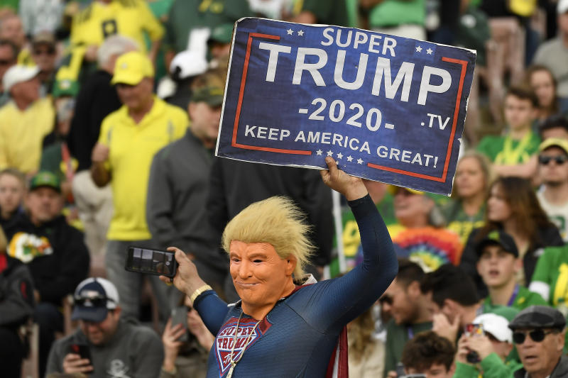 "PASADENA, CALIFORNIA - JANUARY 01: A fan dressed as Super Trump holds up a sign that reads, ""Super Trump 2020 Keep America Great!"" during third quarter in the Rose Bowl game presented by Northwestern Mutual between the Oregon Ducks and the Wisconsin Badgers at Rose Bowl on January 01, 2020 in Pasadena, California. (Photo by Kevork Djansezian/Getty Images)"