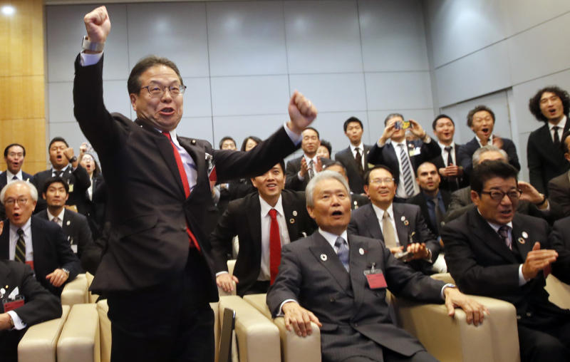 Japan's Economy, Trade and Industry Minister Hiroshige Seko,left, and head of 2025 Japan World Expo committee Sadayuki Sakakibara, center, celebrate after winning the vote at the 164th General Assembly of the Bureau International des Expositions (BIE) in Paris, Friday, Nov. 23, 2018. Japan's Osaka will host the World Expo in 2025, beating out Russia, Azerbaijan for an event that attracts millions. (AP Photo/Christophe Ena)