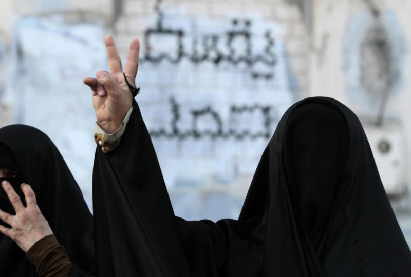 "Bahraini anti-government protesters gesture during a small demonstration in Karzakan, Bahrain, on Saturday, Oct. 13, 2012, calling for the release of residents of the western village jailed in connection with unrest. Graffiti on the wall behind them reads: ""down Hamad,"" referring to Bahrain's king. (AP Photo/Hasan Jamali)"