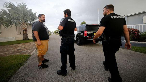 PHOTO: Vero Beach police officers talk to resident Todd Dufresne, left, as they notify residents of a trailer park community of a mandatory evacuation, in preparation for Hurricane Dorian, in Vero Beach, Fla., Sept. 2, 2019. (Gerald Herbert/AP)