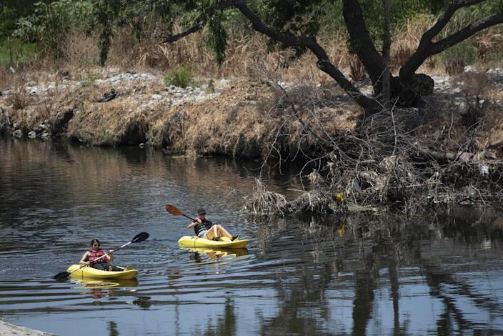 Kayakers float on the Los Angeles River