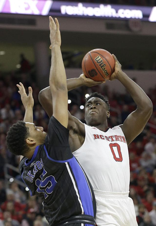 Duke's Jahlil Okafor, left, defends as North Carolina State's Abdul-Malik Abu (0) shoots during the first half of an NCAA college basketball game in Raleigh, N.C., Sunday, Jan. 11, 2015. (AP Photo/Gerry Broome)
