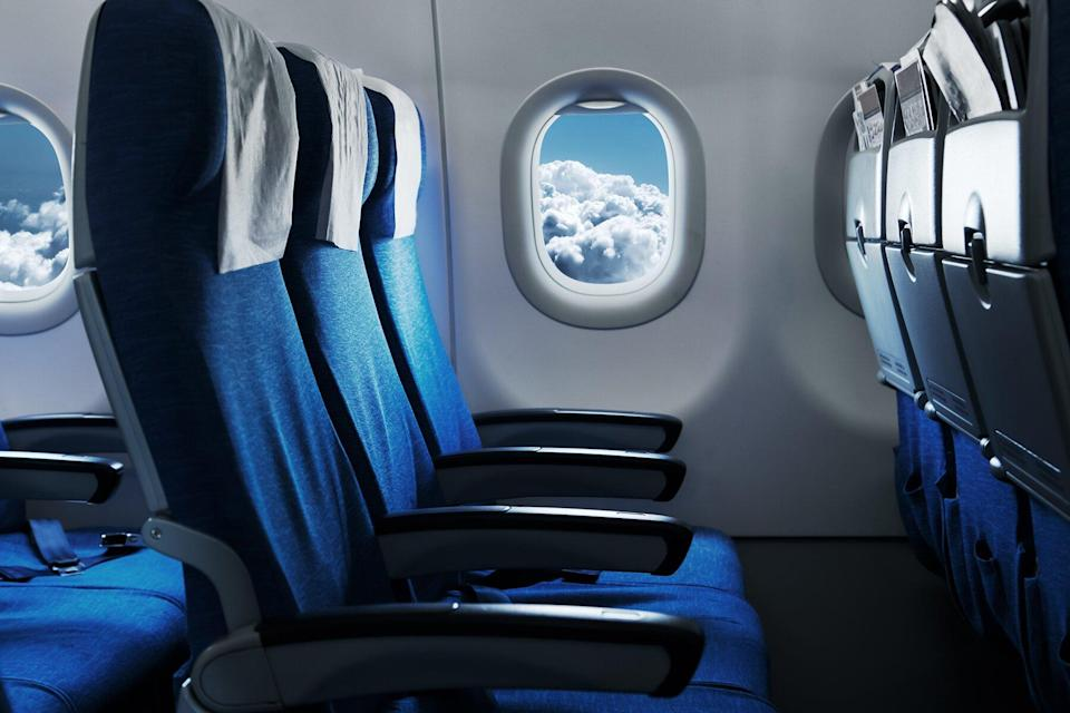 Empty air plane seats. Blue sky and clouds in the window. Airplane interior