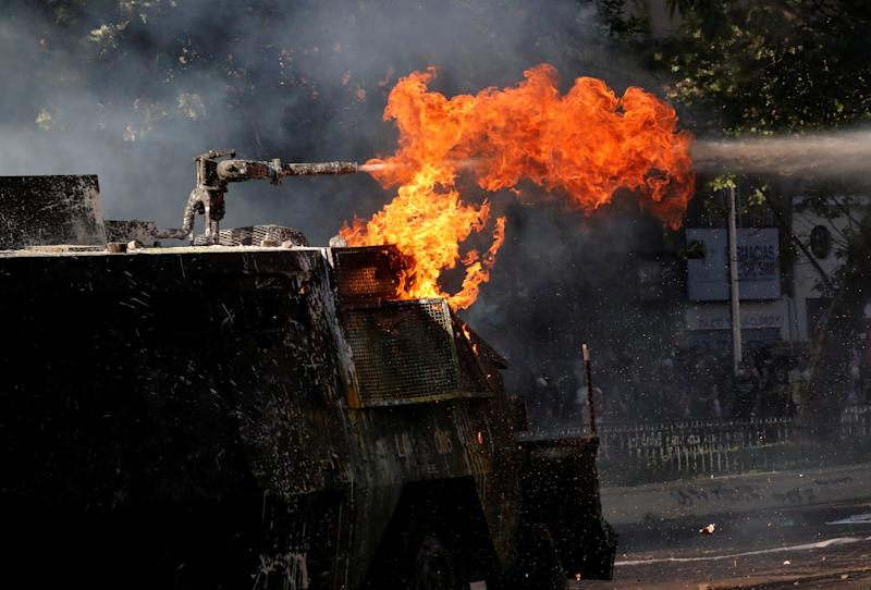 A riot police vehicle with flames uses its water cannon during an anti-government protests in Santiago, Chile on Oct. 28, 2019. (Photo: Henry Romero/Reuters)