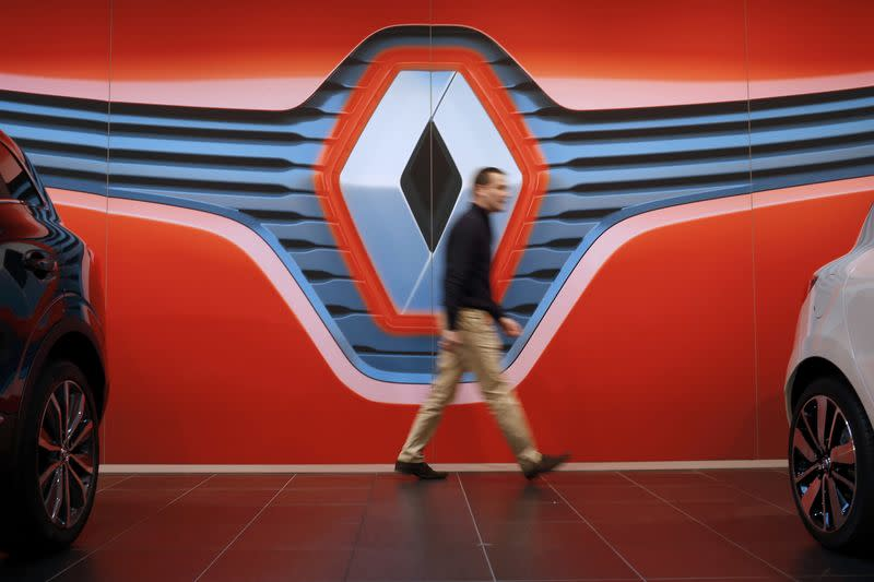 A man walks in front of a Renault logo at a dealership in Saint-Herblain near Nantes