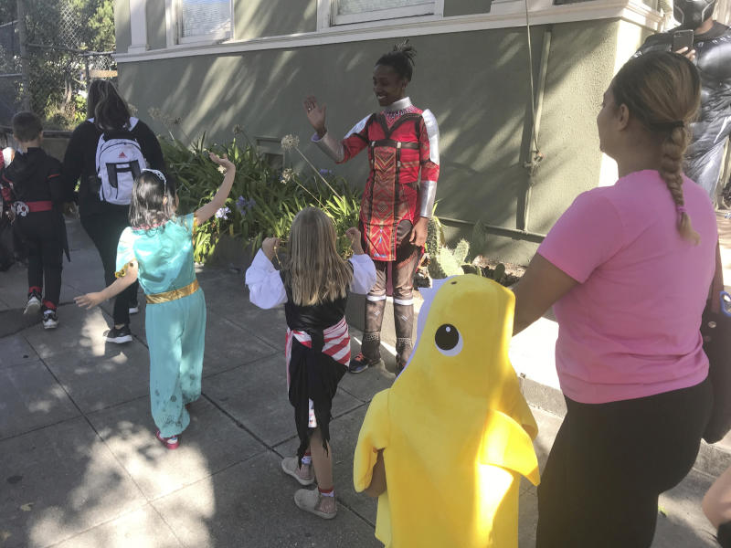 Berkeley Unified School District employee Nikkya Harris, dressed as Okoye from Black Panther, waves at students of Washington Elementary during their annual Halloween Parade on Thursday, Oct. 31, 2019, in Berkeley, Calif. The school had considered holding the parade indoors if the air quality was questionable because of a massive wildfire in Northern California's wine country. For tens of thousands of children in California, the biggest monsters this Halloween are wildfires that have thrown trick-or-treating into disarray. (AP Photo/Liz Schultz)
