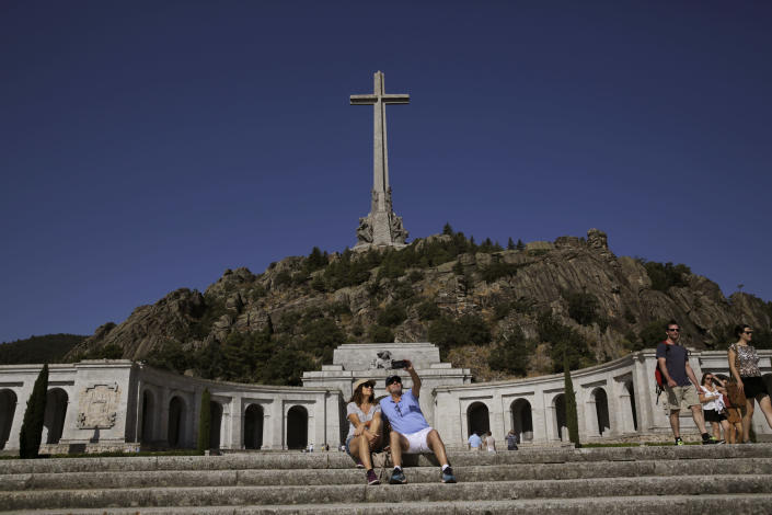 A couple take a photo at the Valley of the Fallen monument at El Escorial, in El Escorial, Spain, Friday, Aug. 24, 2018. Spain's center-left government has approved legal amendments that it says will ensure the remains of former dictator Gen. Francisco Franco can soon be dug up and removed from a controversial mausoleum. (AP Photo/Andrea Comas)