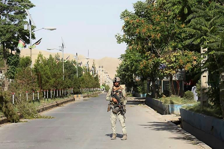 An Afghan soldier stands guard along a road in Qala-i- Naw