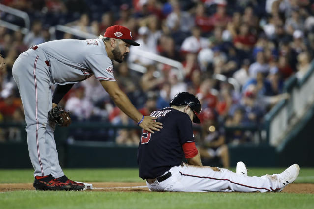 Cincinnati Reds third baseman Eugenio Suarez, left, talks with Washington Nationals' Brian Dozier after they collided on a play at third base during the seventh inning of a baseball game at Nationals Park, Tuesday, Aug. 13, 2019, in Washington. Dozier was out on the tag at the play. The Nationals won 3-1. (AP Photo/Alex Brandon)