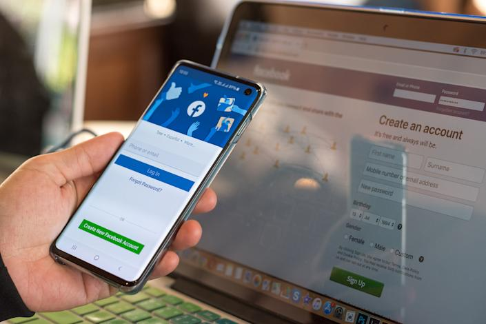 Bangkok, Thailand - July 14th, 2019: Facebook signup web page app on smart phone Samsung Galaxy S10 with user sign in registration screen using social networking and computer notebook from anywhere office.