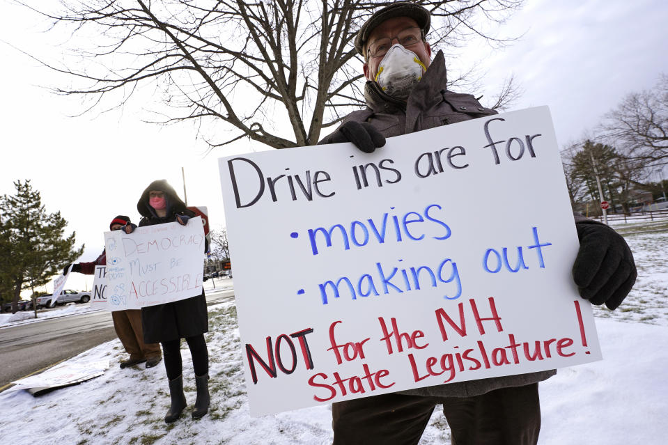 Dennis Jakubowski, of Loudon, N.H., right, protests as state representatives arrive for an outdoor meeting of the New Hampshire House of Representatives in a parking lot, due to the COVID-19 virus outbreak, at the University of New Hampshire Wednesday, Jan. 6, 2021, in Durham, N.H. (AP Photo/Charles Krupa)