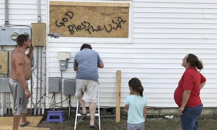 """<span class=""""element-image__caption"""">Mercedes O'Neill and her boyfriend, Kelly Johnson, and neighbor Shawn Dalton put plywood on the window of their home in North Myrtle Beach, South Carolina.</span> <span class=""""element-image__credit"""">Photograph: Jeffrey Collins/AP</span>"""