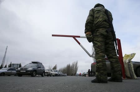 A member of the armed forces of the separatist self-proclaimed Donetsk People's Republic guards a border crossing point as cars queue to drive into the territory of Russia outside the village of Uspenka, Donetsk region, February 8, 2015. REUTERS/Maxim Shemetov