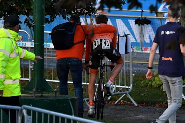 Nils Eekhoff was led away by a member of the Dutch team after the men's under-23 road race at the World Championships. He was disqualified for unauthorized assistance from his team car (AFP Photo/Ben STANSALL)