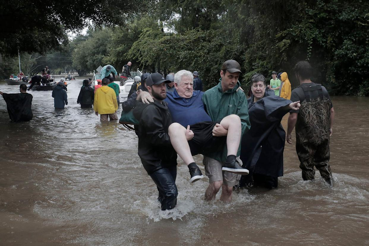 Police and volunteers rescue residents flooded by the San Jacinto river in Kingwood, Texas.