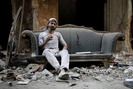 Abu Nimr, 36, smokes a cigarette as he sits on a sofa along a damaged street in Yarmouk Palestinian camp in Damascus, Syria October 10, 2018. Picture taken October 10, 2018. REUTERS/Omar Sanadiki
