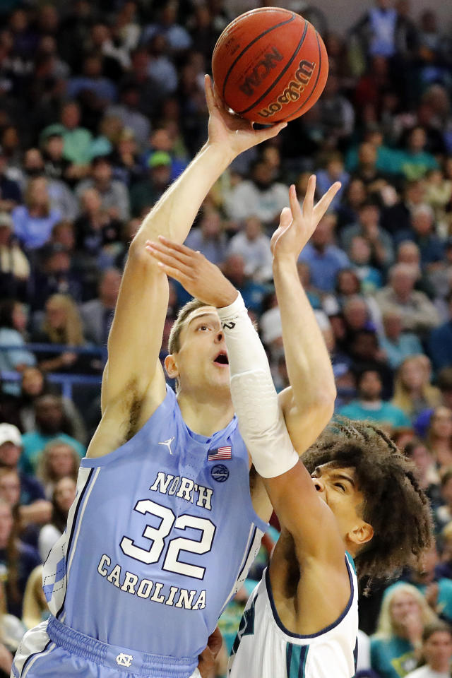 North Carolina's Justin Pierce (32) drives to the basket past Shykeim Phillips (2) during the first half of an NCAA college basketball game in Wilmington, N.C., Friday, Nov. 8, 2019. (AP Photo/Karl B DeBlaker)