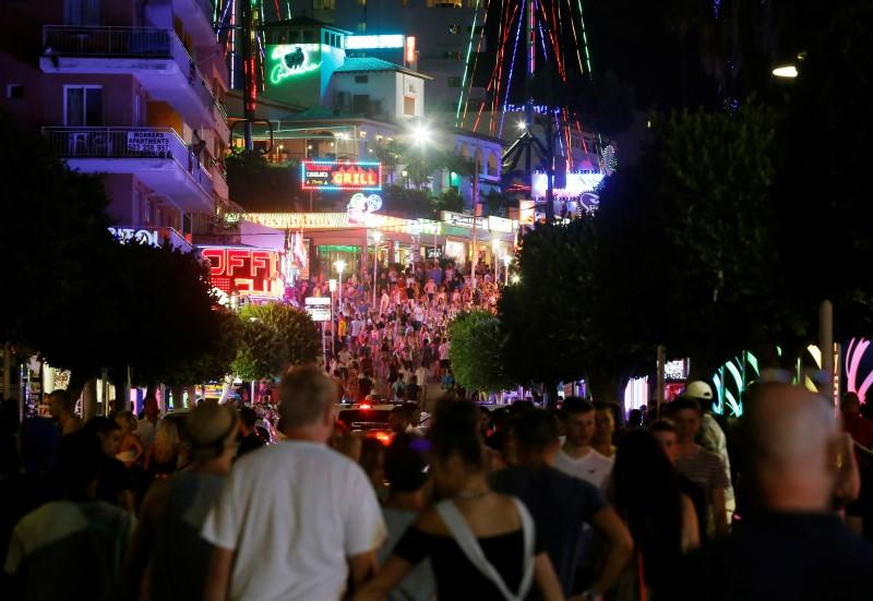 FILE PHOTO: Tourists walk at Punta Ballena street in Magaluf, on the Spanish Balearic island of Mallorca