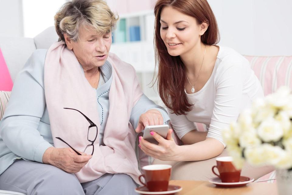 Smiling daughter showing smartphone to senior woman while drinking tea