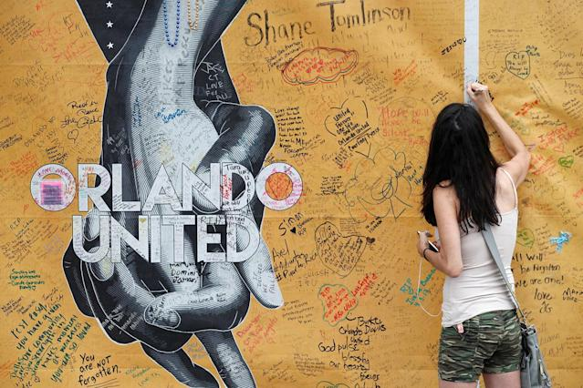 <p>Mary Beth Nickerson signs the wall outside of Pulse Nightclub while visiting the memorial on the one year anniversary of the shooting in Orlando, Florida June 12, 2017. (REUTERS/Scott Audette) </p>