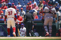 Umpire Brian O'Nora, center, runs into the Philadelphia Phillies dugout while Phillies' Odubel Herrera is at bat during the first inning of a baseball game against the Washington Nationals, Sunday, June 6, 2021, in Philadelphia. O'Nora left the game. (AP Photo/Chris Szagola)