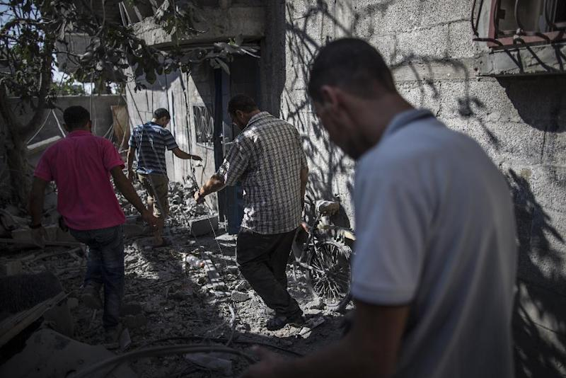 Palestinians walk amidst debris in the Bureij refugee camp in the central Gaza Strip, on August 1, 2014